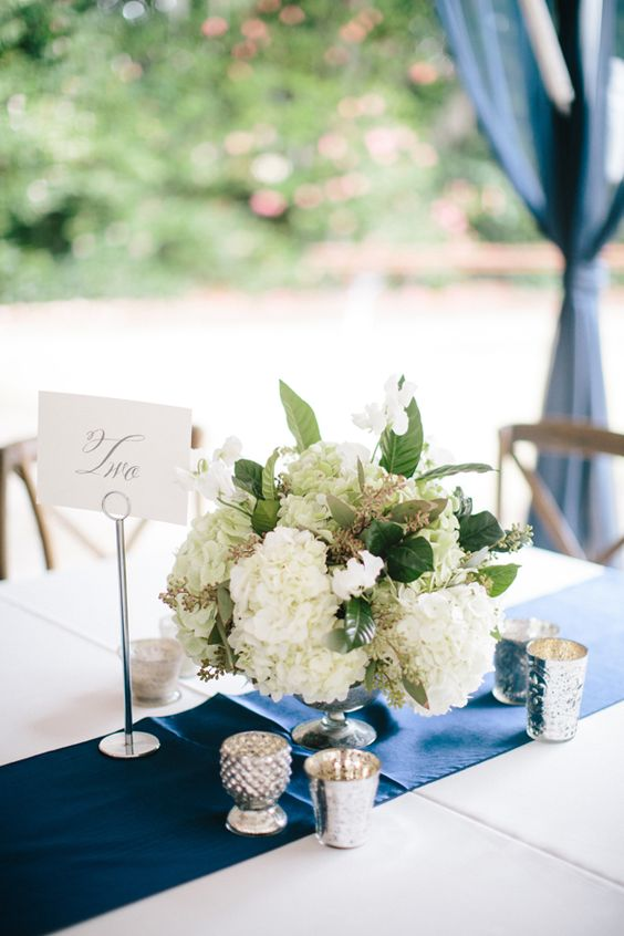 a chic table setting with a white hydrangea wedding centerpiece, candles and a navy table runner