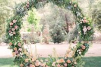 a circle spring wedding arch decorated with greenery and peachy and pink blooms all around