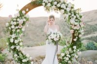 a circle spring wedding arch decorated with lush greenery and white and pink blooms is a trendy idea