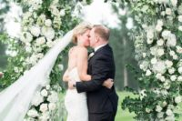 a classic greenery and white bloom wedding arch will work for any season and any wedding theme