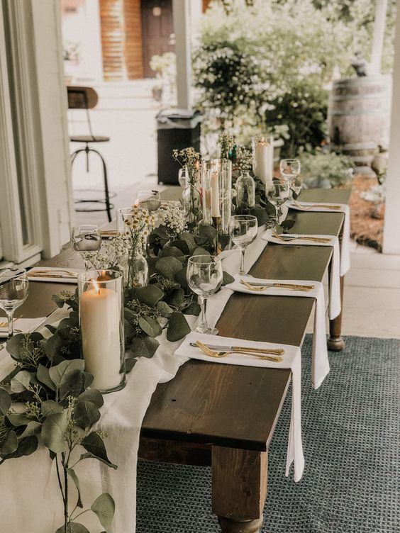a classic wedding table setting with white linens, a lush greenery runner, candles and daisy centerpieces plus gold cutlery