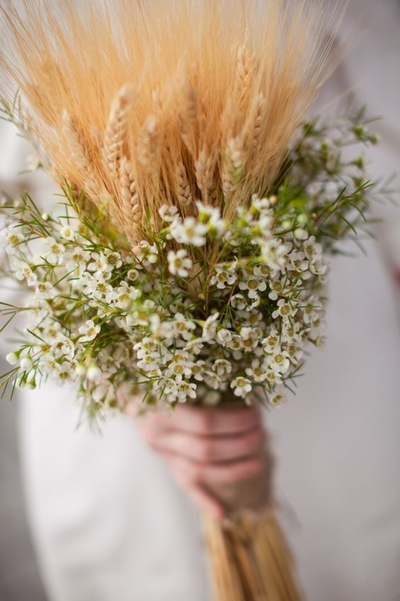 a cool boho summer or rustic summer wedding bouquet with wax blooms and wheat is a lovely idea that won't break the bank