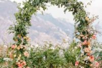 a cool spring wedding arch covered with greenery and decorated with peachy and coral blooms