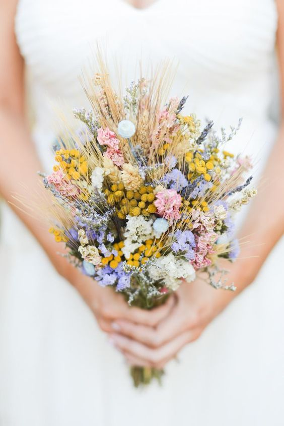 a cool summer wedding bouquet with yellow, pink, purple blooms, whear is amazing for a boho wedding