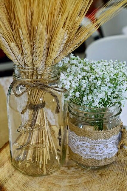 a cute rustic wedding centerpiece of jars with wheat and baby's breath placed right on a wood slice is amazing