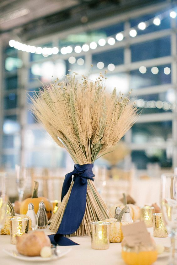 a cute wheat wedding centerpiece with dried blooms and pumpkins around is a cool idea for a rustic fall wedding