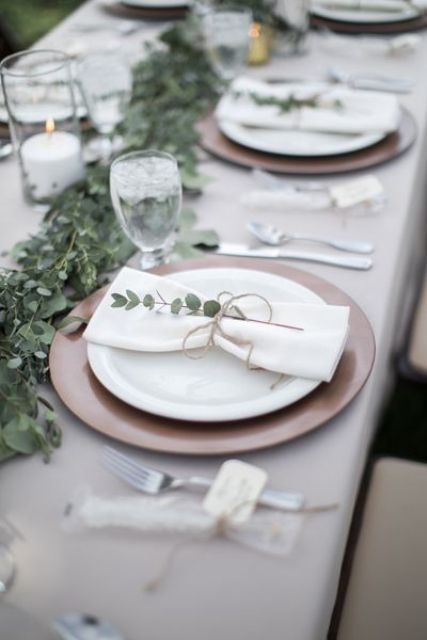 a delicate backyard wedding table setting with neutral linens, a porcelain charger and white plates, a eucalyptus runner