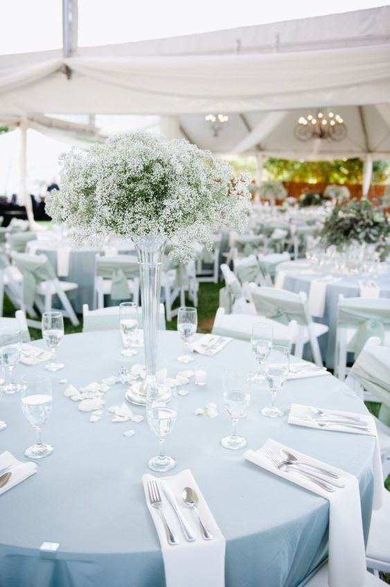 a delicate backyard wedding tablescape with a blue tablecloth, white napkins and a tall baby's breath centerpiece plus petals on the table