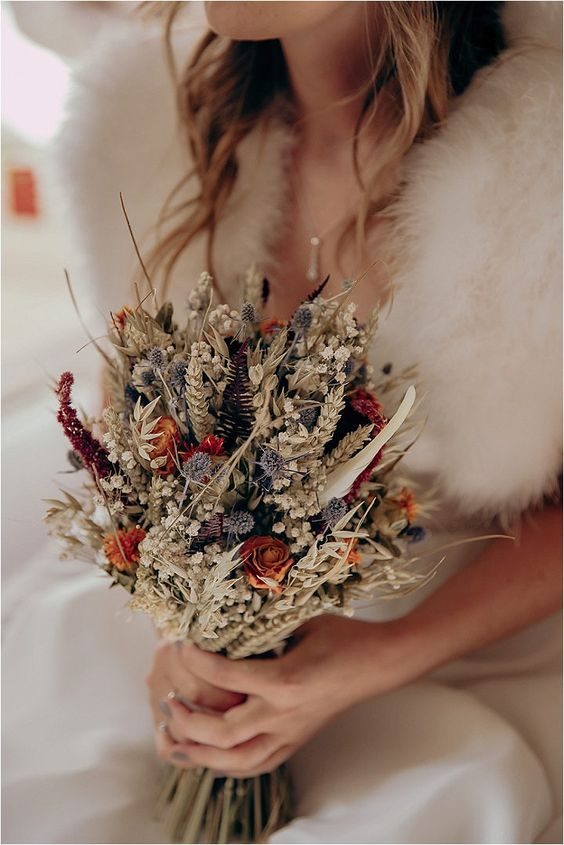 a dried boho wedding bouquet with wheat, orange roses, amaranthus, dried foliage and grasses is amazing and out of the box