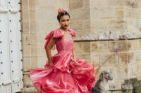 a fabulous pink satin wedding dress with a layered skirt and bow sleeves looks statement-like