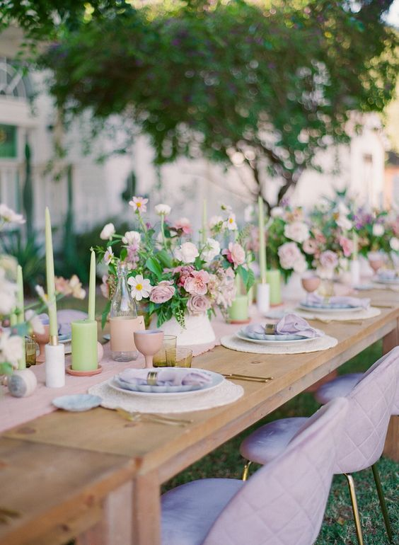 a fun pastel backyard wedding tablescape with a pink runner, pink blooms and goblets, green candles and greenery plus lilac napkins
