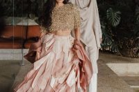a gold fully embellished crop top with short sleeves, a pink layered petal skirt with a train for a glam look