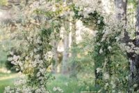 a gorgeous spring wedding arch fully done with white blooming branches just screams spring and blooms