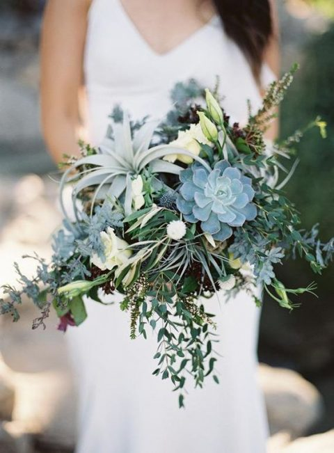 a greenery cascading wedding bouquet with succulents, air plants and foliage plus some white roses for a cooler look