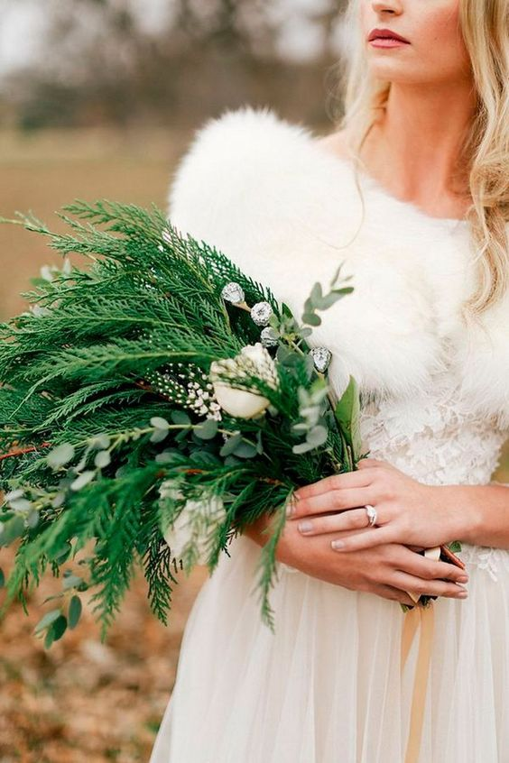 a greenery wedding bouquet with some berries and white blooms with a catchy relaxed shape