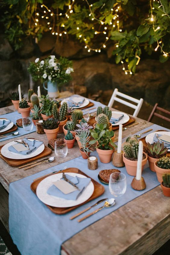 a lovely backyard wedding tablescape with blue linens, wooden placemats, potted succulents and cacti plus candles