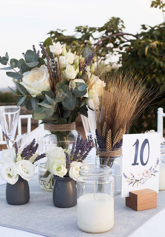 a lovely cluster wedding centerpiece of white roses, eucalyptus, wheat, lavender, candles and a table number is chic and cool