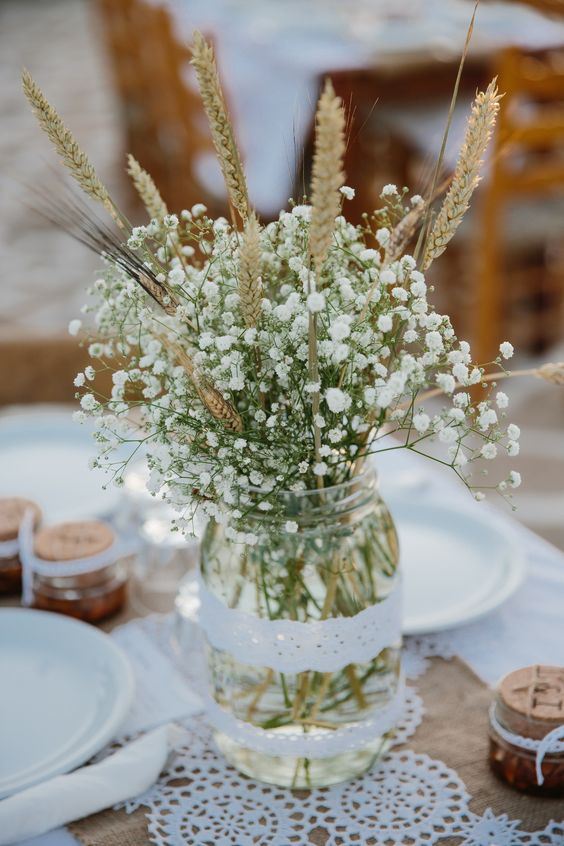 a lovely rustic wedding centerpiece of a jar with baby's breath and wheat is a simple and cool idea for a fall rustic wedding