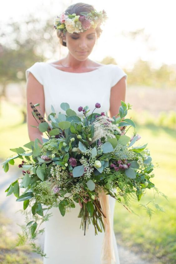 a lush summer wedding bouquet with lots of greenery, small pink blooms and feathers is a bold idea