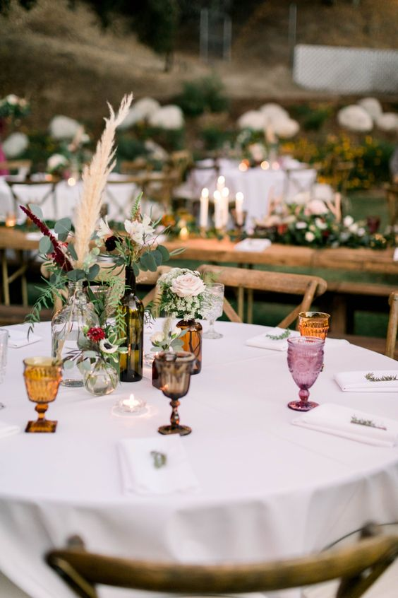 a modern boho backyard wedding tablescape with colorful glasses, pastel blooms with greenery and pampas grass plus candles