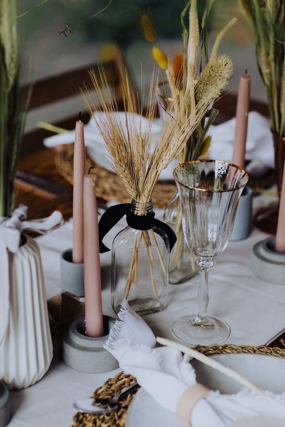 a modern cluster wedding centerpiece of colorful bunny tails, wheat and blush candles is ideal for a modern rustic wedding