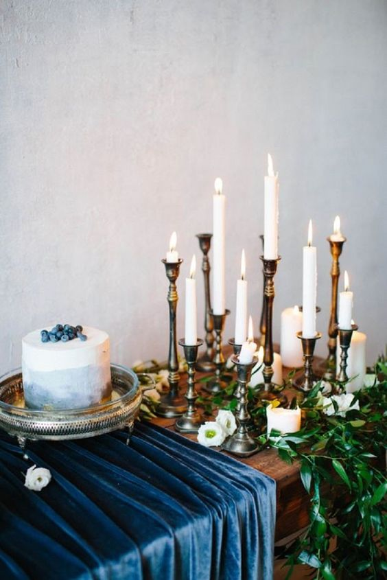 a navy ombre wedding cake topped with blueberries, a navy velvet table runner and lots of white candles