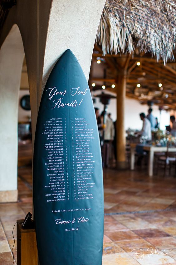 a navy surfing board with white letters is a great and cool wedding seating chart for a tropical or surf wedding