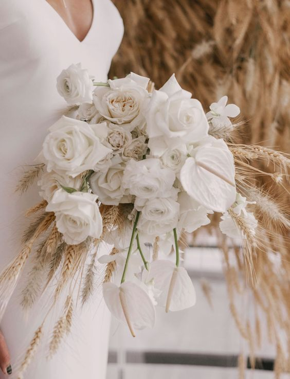 a non-typical wedding bouquet of white roses, peony roses, callas and wheat is a fresh and bold idea for a modern rustic wedding