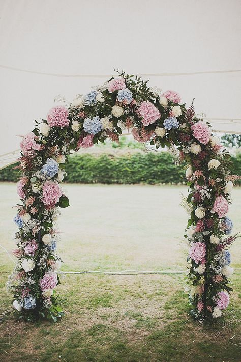 a pastel spring wedding arch of foliage, pink and blue hydrangeas for a romantic look