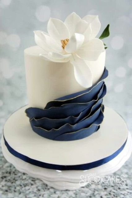 a plain white wedding cake with navy ruffles, a large white sugar bloom on top is very chic