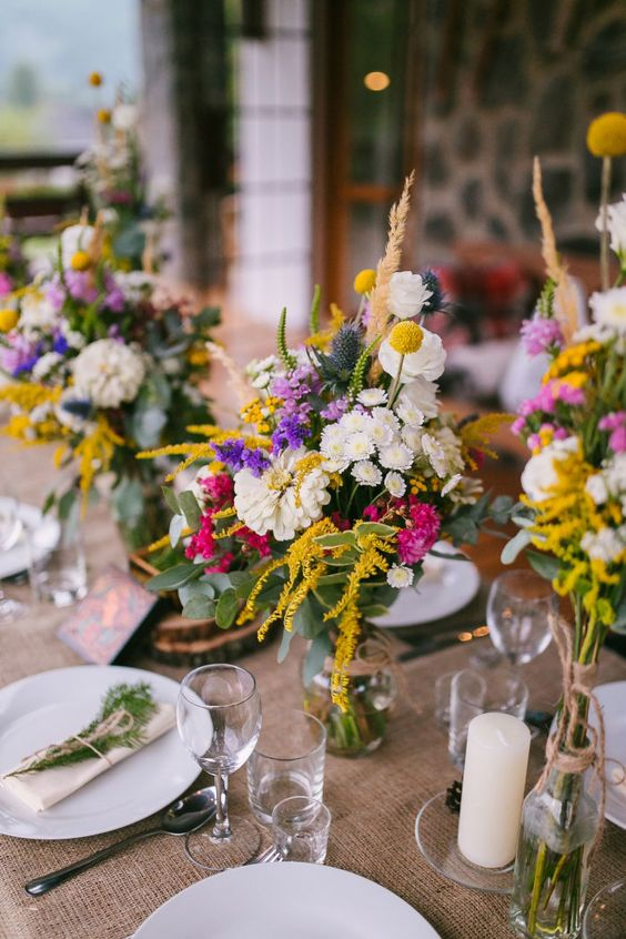 a pretty rustic backyard wedding tablescape with a burlap runner, bright blooms and greenery, pillar candles and wood slices