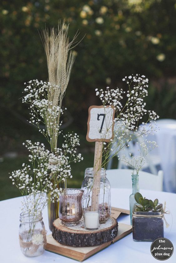a pretty rustic summer wedding centerpiece of a wood slice, baby's breath and wheat, a candle holder and a potted succulent