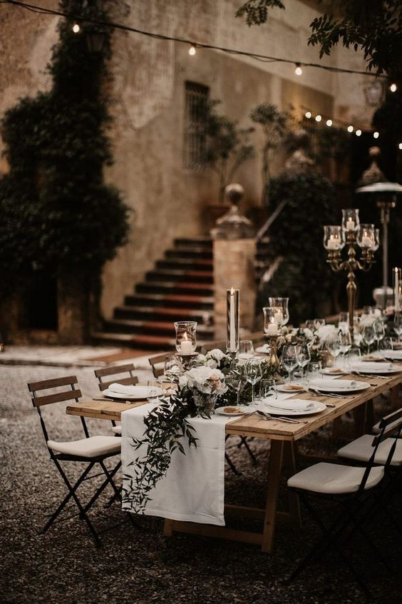a refined backyard wedding tablescape with neutral linens, neutral blooms and greenery, chic candles and candelabras is amazing