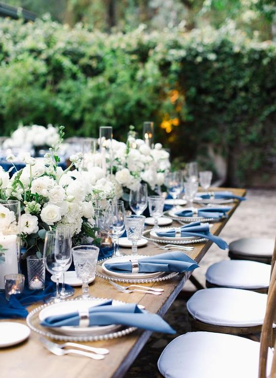 a refined navy and white wedding table setting with a navy table runner, white floral centerpieces, navy napkins and silver