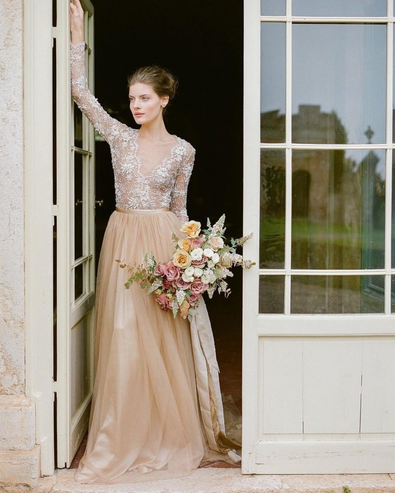 a refined nude and white lace top with long sleeves and a tan pleated maxi skirt for a very chic and beautiful look