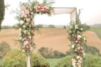 a refined wedding arch made of branches, neutral fabric, pink and hot pink blooms and greenery plus candle lanterns