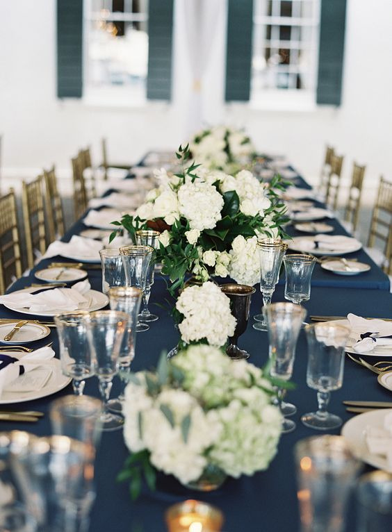 a refined wedding table setting with a navy tablecloth, white napkins, white hydrangeas and touches of gold