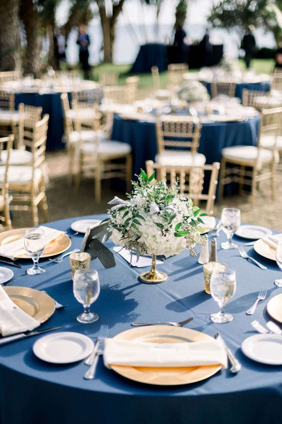 a refined wedding tablescape with a navy tablecloth, gold chargers and candle lanterns and a white floral centerpiece