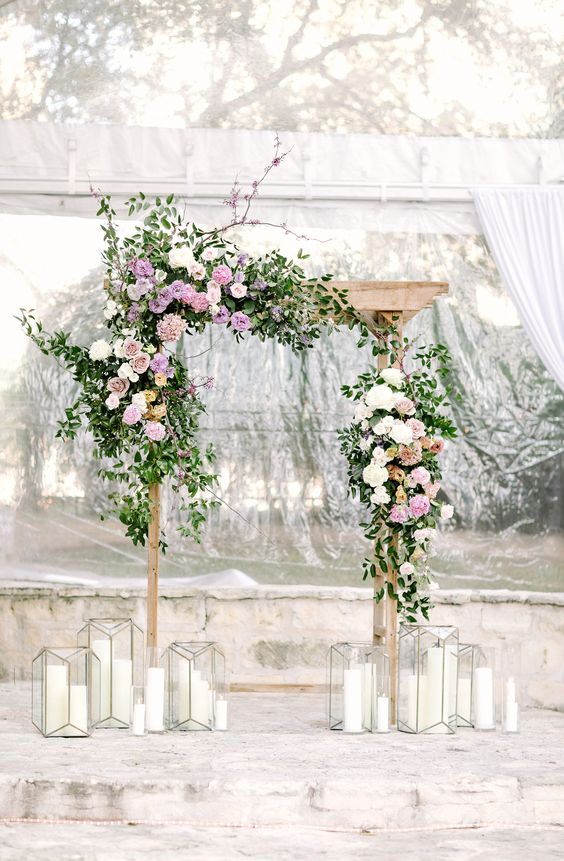a refreshing spring wedding arch done with greenery and neutral and lilac blooms and candle lanterns