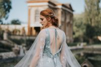 a romantic celestial pale blue wedding dress with star embroidery, an open back and a capelet