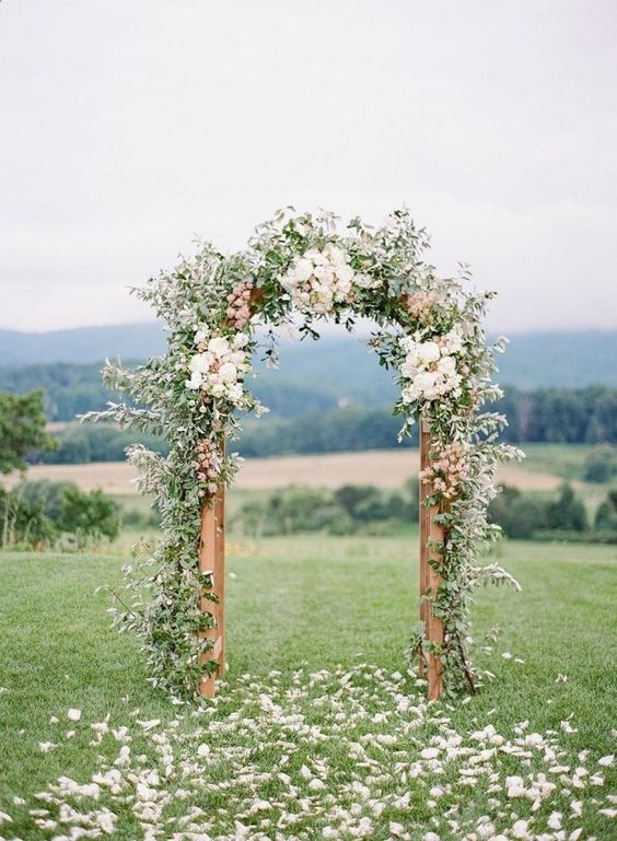 a romantic spring wedding arch done with greenery and neutral and blush blooms looks cool