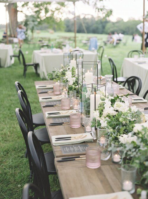 a rustic backyard wedding table setting with an uncovered table, white blooms and greenery, candle lanterns and blush glasses plus black cutlery