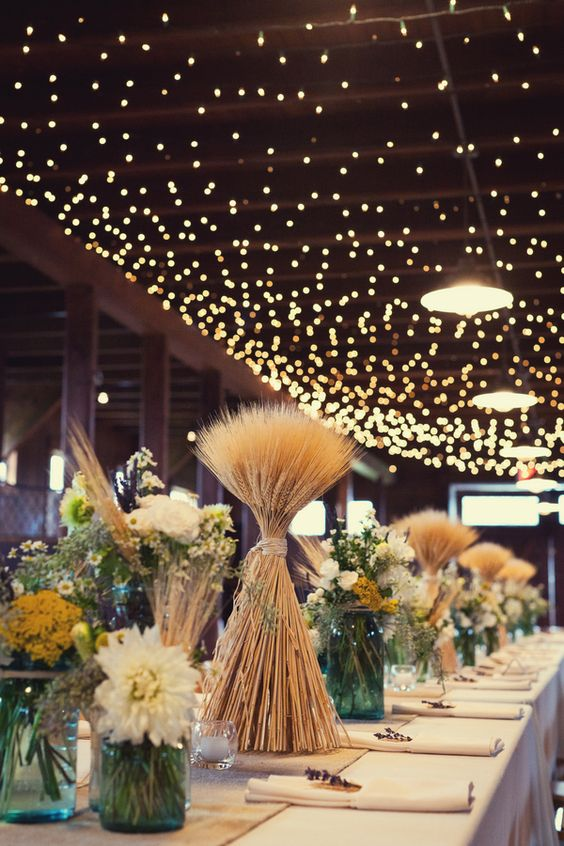 a rustic wedding tablescape with wheat arrangements, white and yellow blooms in jars and candles around is super cool