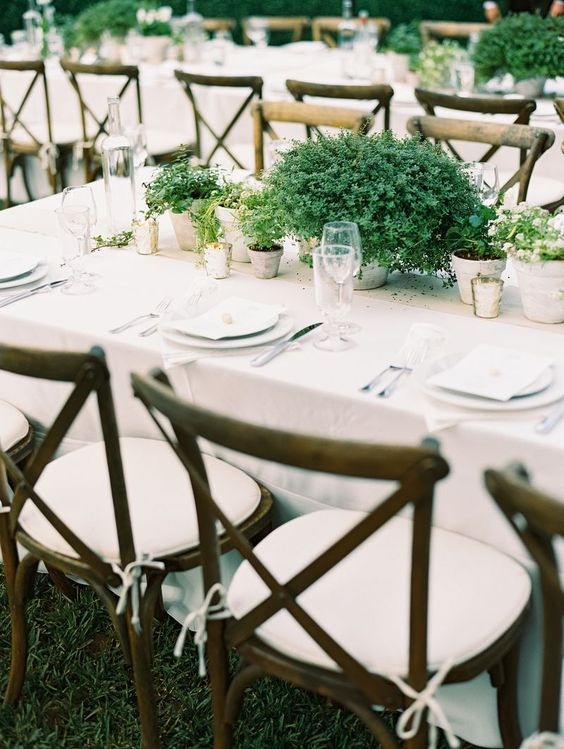 a simple and lovely backyard wedding table setting with potted greenery centerpieces and candles, neutral plates and linens and white chairs