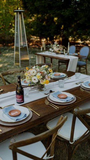a simple and pretty backyard wedding tablescape with white and blue linens, bold blooms and gold cutlery is all cool