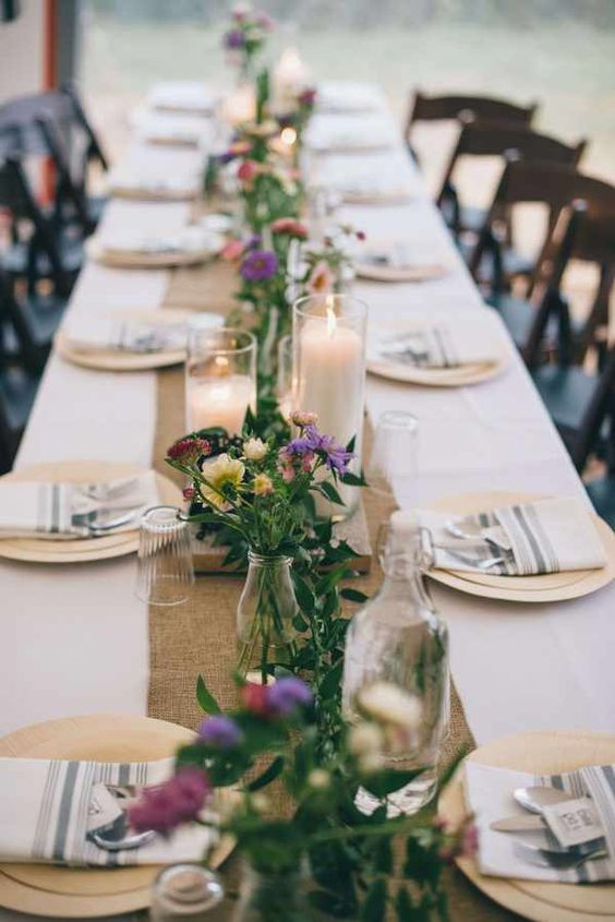 a simple and stylish backyard wedding tablescape with striped napkins, a burlap runner, bright blooms and greenery and candles is gorgeous