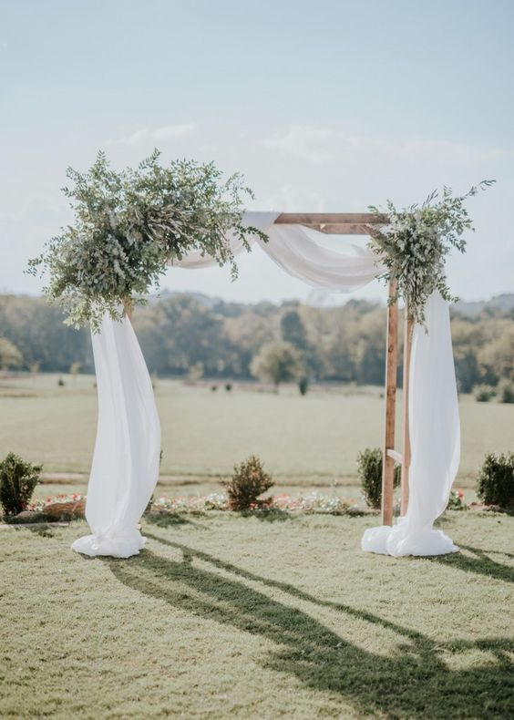 a simple rustic spring wedding arch with flowy white fabric and lots of greenery looks fresh and cool