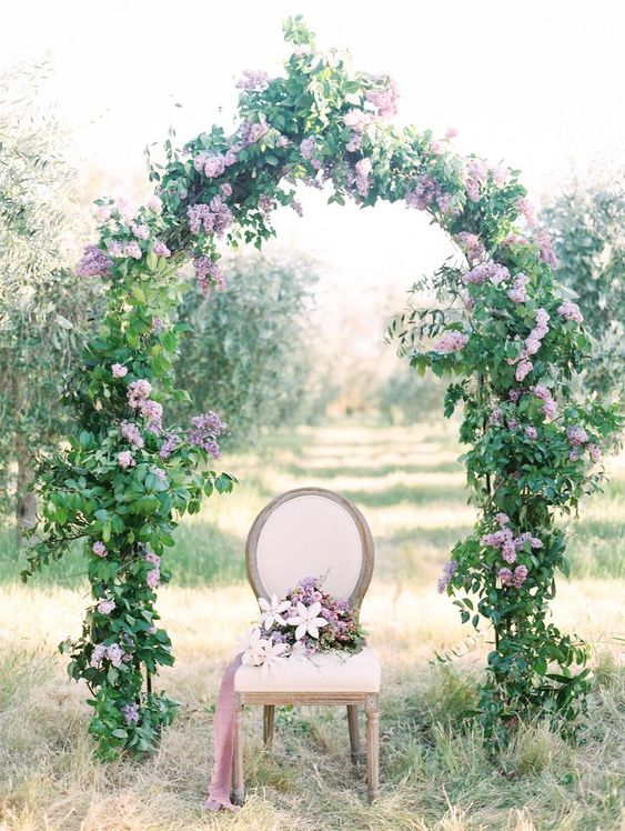 a spring wedding arch covered with greenery and spruced up with lilac and purple blooms is gorgeous