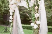 a spring wedding arch done with sheer fabric, greenery and neutral and blush blooms and branches