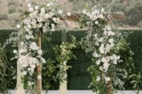 a spring wedding arch with greenery and lush white blooms is a chic idea for a modern or rustic ceremony outdoors